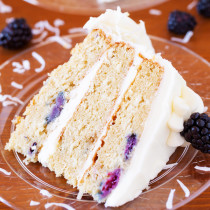 A cake for all occasions, this Blackberry Coconut Cake has a dense and moist crumb of blackberries and coconut, is filled with rich coconut buttercream, and frosted with tangy cream cheese frosting. Perfect for berry and coconut lovers everywhere.