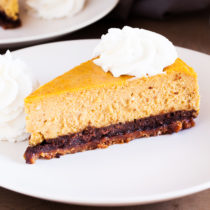 A gingersnap cookie crust, a layer of chocolate cake, and creamy pumpkin cheesecake make this the Ultimate Pumpkin Cheesecake.