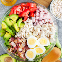A Classic Cobb Salad loaded with fresh vegetables, three kinds of meat, hard boiled eggs, and blue cheese crumbles.